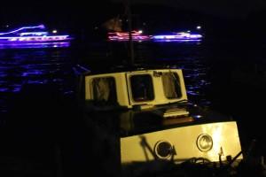 Lit boats glide past Djes